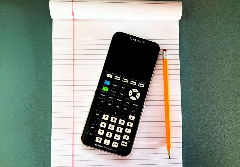 graphing calculator on desk with notebook and pencil