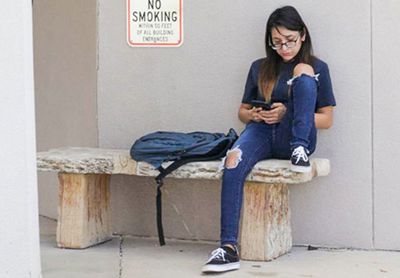 female student sitting on an outdoor bench looking at cellphone