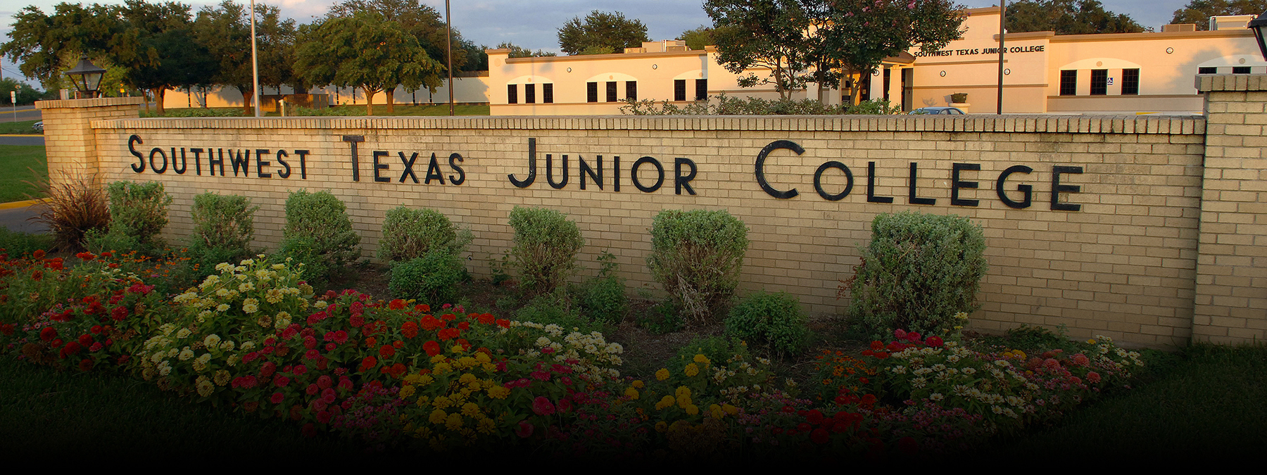 Uvalde's Southwest Texas Junior College brick wall entrance with colorful flowers planed in front of it